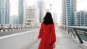 Het meisje met zwart schitterend haar in een lange heldere rode kleding loopt over de brug in de Jachthaven van Doubai stock video