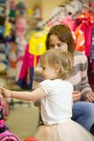 Het meisje in mooie kleding en haar mamma bij de kinderen` s kleren winkelen Royalty-vrije Stock Afbeeldingen