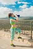 Het meisje na lang - in werking gesteld dranken koud water van een thermosfles royalty-vrije stock fotografie
