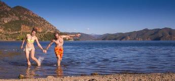 Het meisje in nationale kleding op het meer Stock Foto