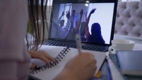 Het meisje neemt aan videogesprek gebruikend laptop computer voor onderwijs online en verre het werk bespreking deel die nota's b stock footage