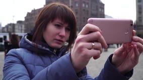 Het meisje neemt beelden op een smartphone op Damvierkant bekende centrale plaats in Amsterdam stock videobeelden