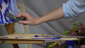 Het meisje neemt blauwe olieverf van het palet en spreidt het op het canvas met een spatel uit stock video