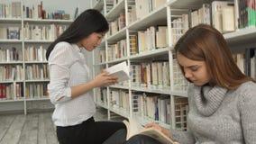 Het meisje neemt boek van de plank bij de bibliotheek stock videobeelden