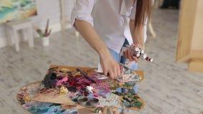Het meisje neemt de buizen van verf op die op het palet liggen School van Art. stock videobeelden