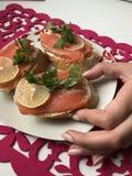 Het meisje neemt de sandwich van de plaat Sandwiches met zalm, met greens en citroen worden verfraaid die Sandwiches op een plaat Royalty-vrije Stock Afbeeldingen