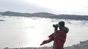 Het meisje neemt een foto van bevroren meer stock videobeelden