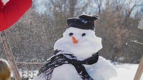 Het meisje neemt een neus op de sneeuwman op De kindspelen met een sneeuwman De winter gelukkige tijd, jong geitje op sneeuw stock videobeelden