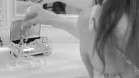 Het meisje neemt een parelhalsband Hij zit dichtbij een spiegel elegant luxebinnenland stock footage