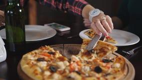 Het meisje neemt een plak van pizzaplaten in het restaurant Vrolijk bedrijf in de pizzeria stock video