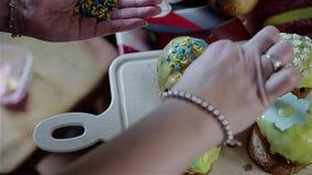 Het meisje neemt een snoepje bestrooit van haar hand en versiert haar kleine Pasen-cakes Mooi behandel stock videobeelden