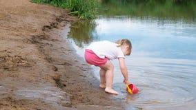 Het meisje neemt en giet water uit de emmer op in het zand Het spelen van het kind op het strand stock footage