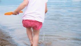 Het meisje neemt en giet water uit de emmer op in de zandclose-up Het spelen van het kind op het strand stock footage