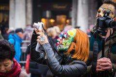 Het meisje neemt foto's terwijl het dragen van een kleurrijk masker Stock Foto