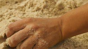 Het meisje neemt het overzeese zand in haar hand stock video