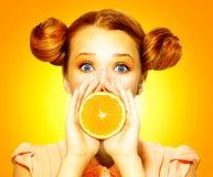 Het meisje neemt sappige sinaasappel Stock Afbeeldingen