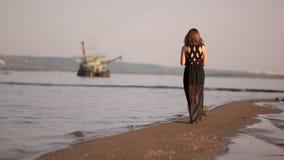 Het meisje neemt shells en kiezelstenen op de kust op het strand stock video