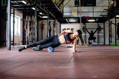 Het meisje oefent op gymnastiekvloer uit Stock Foto