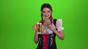Het meisje Oktoberfest trekt en likt seksueel zijn lippen aan Het groene scherm stock video