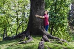 Het meisje omhelst boom Stock Foto's