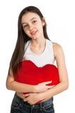 Het meisje omhelst een hoofdkussen in de vorm van hart stock fotografie