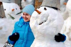 Het meisje omhelst een vrolijke sneeuwbal stock foto's