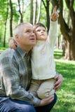 Het meisje omhelst grootvader, zit op wapens en Royalty-vrije Stock Afbeelding