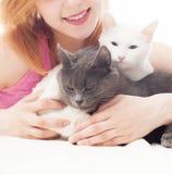Het meisje omhelst twee katten Royalty-vrije Stock Afbeeldingen
