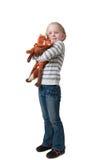 Het meisje omhelst zacht stuk speelgoed Stock Afbeeldingen