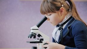 Het meisje onderzoekt aandachtig microscoop stock videobeelden