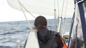 Het meisje onderzoekt de afstand op een jacht stock videobeelden