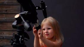 Het meisje onderzoekt de hemel door een telescoop stock video