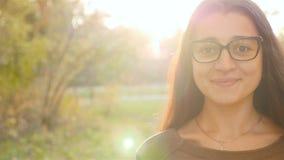 Het meisje onderzoekt de lens Mooie glimlach Close-up stock footage