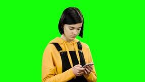 Het meisje onderzoekt de telefoon en ziet vreemde foto's Het groene scherm stock footage