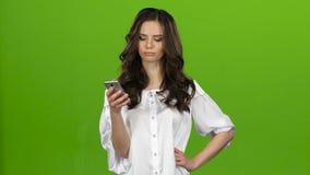 Het meisje onderzoekt de telefoon, selecteert de informatie die zij heeft gewenst Het groene scherm stock footage
