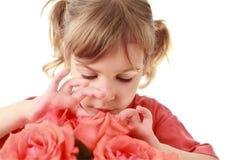 Het meisje onderzoekt en raakt bloemblaadjes van toenam Royalty-vrije Stock Foto