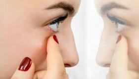 Het meisje onderzoekt haar oog voor de spiegel royalty-vrije stock fotografie