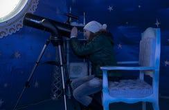 Het meisje onderzoekt telescoop in de herenhuisvader Frost Royalty-vrije Stock Afbeelding