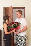 Het meisje ontmoet vriend met bloemen dichtbij de deur Stock Afbeeldingen