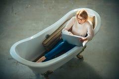 Het meisje ontspant in badkuip met laptop houdt blog Behendige zaken en mededeling Koop online en digitale marketing stock afbeelding