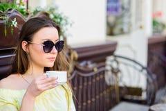 Het meisje ontspant in de kop van de koffiecappuccino Cafe?nedosis Koffie voor energieke succesvolle dag Ontbijttijd in Koffie Me stock fotografie