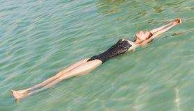 Het meisje ontspant en zwemt in het water royalty-vrije stock afbeeldingen