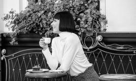 Het meisje ontspant koffie met koffie en dessert Geniet het vrouwen aantrekkelijke elegante brunette van gastronomische het terra stock foto's