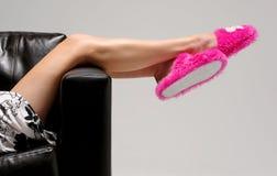 Het meisje ontspant met roze pantoffels stock fotografie