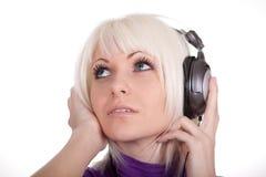Het meisje in oortelefoons luistert aan muziek stock fotografie