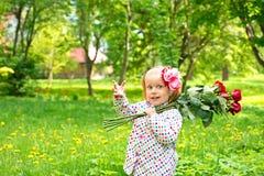 Het meisje op aard met bloemen stock afbeelding