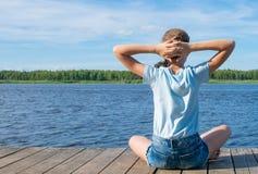 Het meisje op de achtergrond die van de hemel en het water, op de pijler zitten, kruiste haar handen achter haar hoofd en het zon royalty-vrije stock afbeeldingen