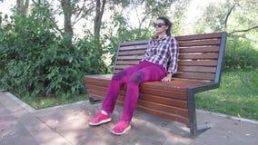 Het meisje op de bank die zijn been schudden stock video
