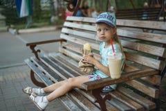 Het meisje op de bank eet straatvoedsel royalty-vrije stock foto