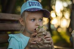 Het meisje op de bank eet straatvoedsel stock fotografie